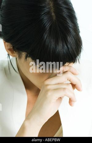 Woman touching bridge of nose, head down