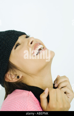 Teen girl wearing knit hat, head back, laughing, portrait - Stock Photo