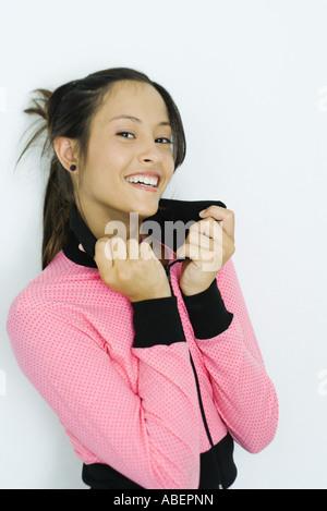 Teen girl wearing sweatshirt, holding up collar, portrait - Stock Photo
