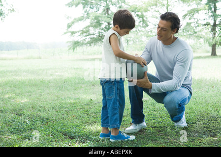 Boy and father talking outdoors, holding ball - Stock Photo