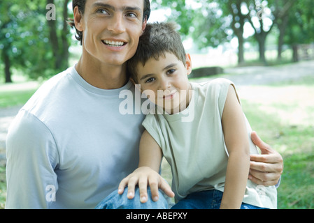 Boy and father, boy sitting on man's lap - Stock Photo