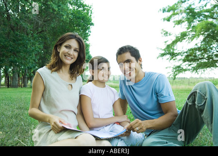 Family sitting outdoors, reading together - Stock Photo