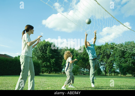 Family outdoors playing volleyball - Stock Photo
