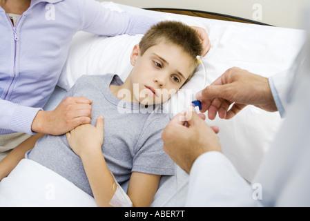 Boy having IV drip adjusted in hospital - Stock Photo