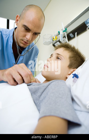 Boy lying in hospital bed, doctor listening to chest with stethoscope - Stock Photo