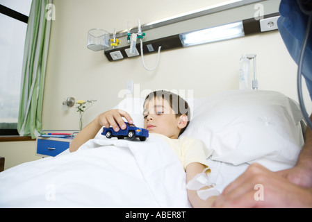 Boy lying in hospital bed, holding toy - Stock Photo
