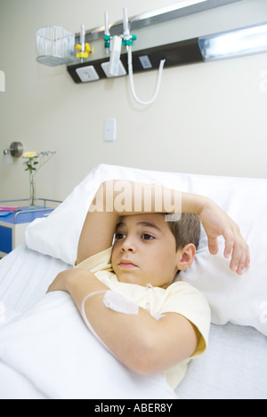Boy lying in hospital bed - Stock Photo