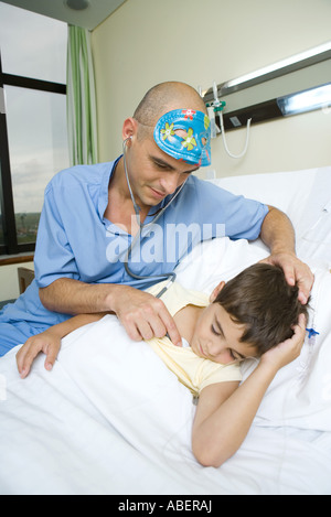Boy lying in hospital bed, sleeping, doctor holding stethoscope to boy's chest - Stock Photo
