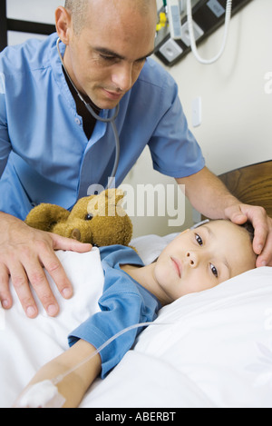 Girl lying in hospital bed, male nurse's hand on girl's forehead - Stock Photo