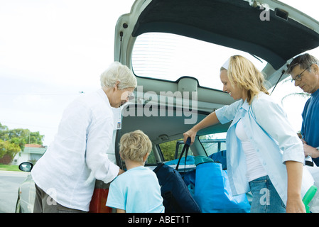 Family unloading trunk of car - Stock Photo