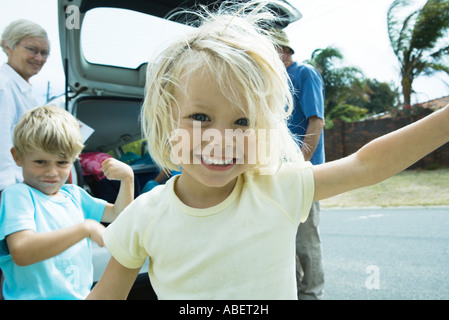 Family unloading trunk of car, focus on little girl in foreground - Stock Photo