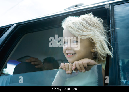 Child sticking head out of car window - Stock Photo