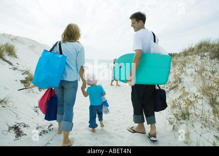 Family walking through dunes to beach - Stock Photo