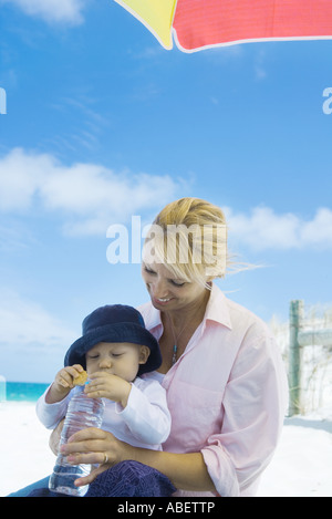 Baby with mother on beach - Stock Photo