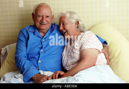 Senior couple smiling in bed - Stock Photo