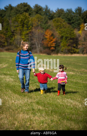 A woman and her young children explore a field on the Common Pasture in Newburyport MA - Stock Photo