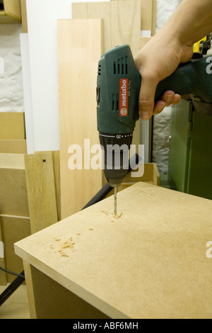 Drilling holes in a cabinet prior to fixing castors - Stock Photo