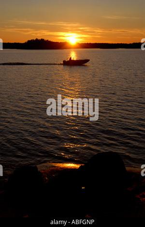 Boat sunset over Sweden - Stock Photo