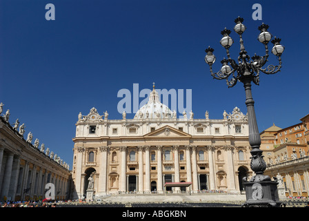 Statues of Saints on roof of Saint Peters Papal Basilica Vatican in Rome Italy with lampost and blue sky - Stock Photo