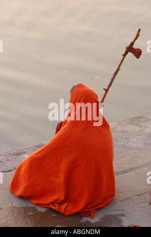 Sadhu sits on the banks of the Ganges during the sunrise - Stock Photo