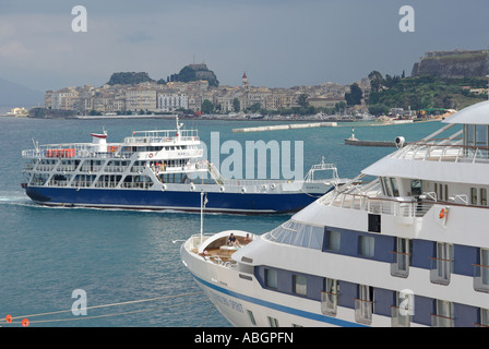 Corfu Greek island Corfu Town new port with cruise ship at moorings and views towards the Old Town Fort ferry boat - Stock Photo