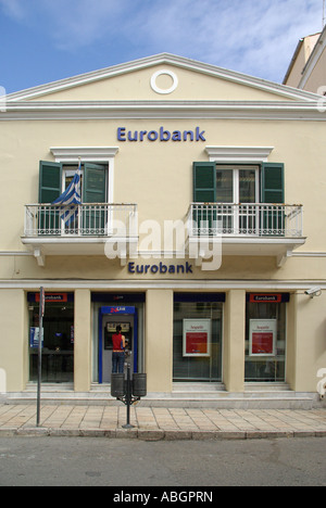 Corfu Town lady using hole in the wall ATM cash machine at  Eurobank branch premises - Stock Photo