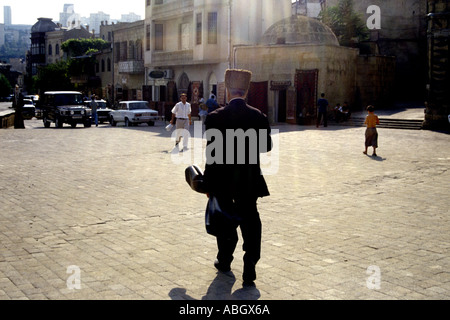 Man with violin and Muslim prayer hat walks past Maiden's Tower in Baku Old Town Azerbaijan - Stock Photo