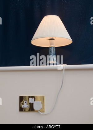 Table lamp with cream lamp shade on white shelf with blue behind plugged into a UK wall socket. England - Stock Photo