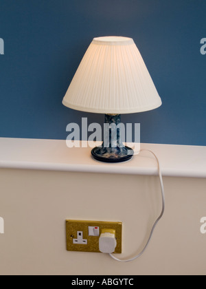 Table lamp lit up lamp shade on white windowsill with blue behind plugged into wall socket showing cable. England - Stock Photo
