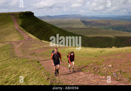 Walkers head for Pen y Fan on pathway in the Brecon Beacons National Park with Corn Du behind Powys Wales UK - Stock Photo