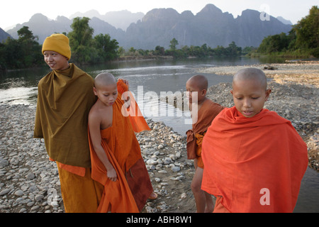 Young monks relaxing by the Nam Song river in Vang Vieng, Laos - Stock Photo