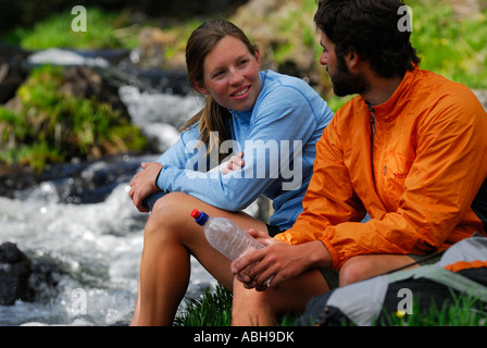 Hiker couple talking while soaking feet in a cold mountain stream hiking in wilderness of Oregon USA - Stock Photo