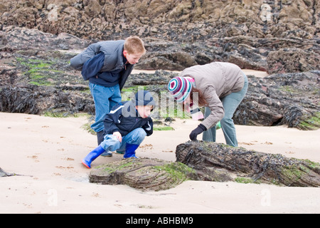 Mum and kids explore beach life in winter Fife Scotland - Stock Photo