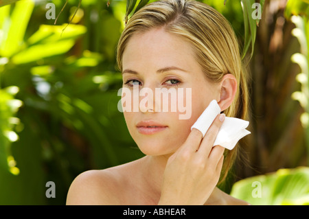 Portrait of a young woman using a cleansing cotton on her face, outdoors - Stock Photo