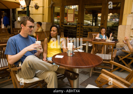 Couple sitting in an open air Cafe at Liszt Square and drinking latte macchiato Pest Budapest Hungary - Stock Photo