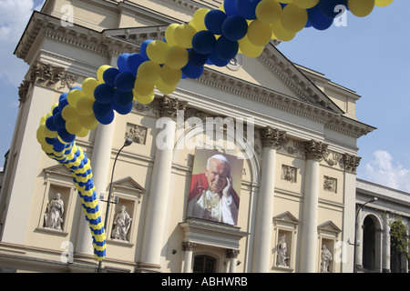 Warsaw Poland image of Pope John Paul II on St Anne Church framed by blue and yellow balloons - Stock Photo