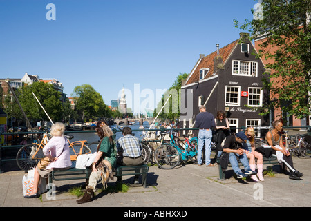 People sitting on bridge near of de Sluyswacht a brown cafe at canal Oude Schans Amsterdam Holland Netherlands - Stock Photo