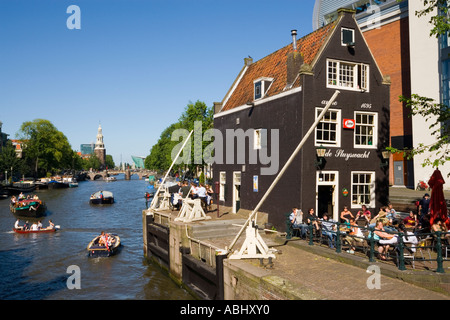 Leisure boats on canal Oude Schans passing de Sluyswacht a typical brown cafe Amsterdam Holland Netherlands - Stock Photo