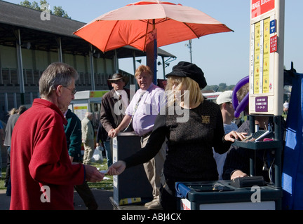 Female bookmaker taking punter's money at Great Yarmouth Races (2007). - Stock Photo
