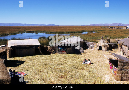 Lake Titicaca, Peru. Typical houses made of reeds on the floating island of Uros with women in traditional dress. - Stock Photo
