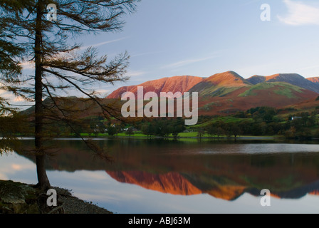 The last rays of autumn sunlight shine on distant mountains that are reflected perfectly in the waters of Lake Buttermere - Stock Photo