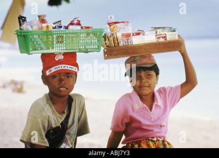 Child vendors on Samur beach Bali - Stock Photo