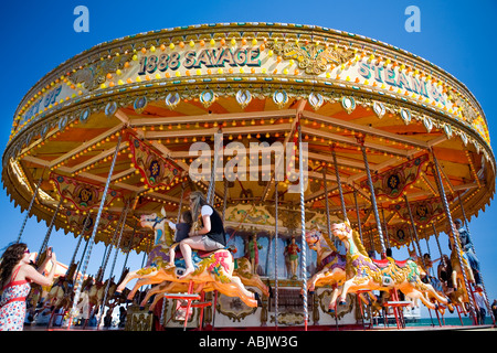 Mother and Baby ride on Vintage Merry go Round on Brighton Seafront while a family member takes their photograph, - Stock Photo