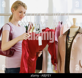 Woman looking at clothing in store - Stock Photo