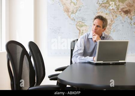 Businessman thinking next to laptop
