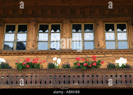 Typical Alpine wooden chalet with red geraniums flowers and lace curtains in Leysin old town in Valais in Switzerland - Stock Photo