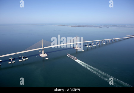 Scenic aerial photo of Sunshine Skyway Bridge and cargo ship passing under Tampa Bay Florida - Stock Photo