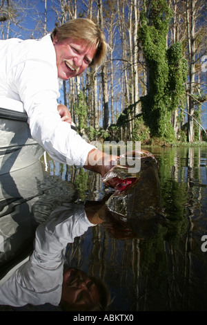 Photo of middle aged excited fisherman pulling his catch large bass out of the water on Central Florida lake - Stock Photo