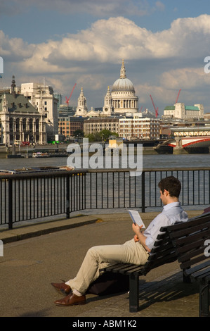 Man reading along the Thames in central London England UK - Stock Photo