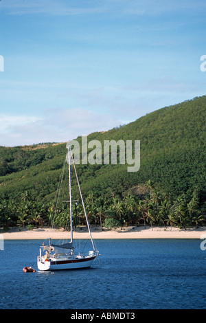 Small sailboat anchors in Laguna of Pacific island - Stock Photo